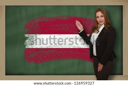 Successful, beautiful and confident woman showing flag of latvia on blackboard for marketing research, presentation and tourist advertising - stock photo