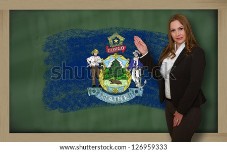 Successful, beautiful and confident woman showing flag of maine on blackboard for marketing research, presentation and tourist advertising - stock photo