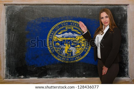 Successful, beautiful and confident woman showing flag of nebraska on blackboard for marketing research, presentation and tourist advertising - stock photo