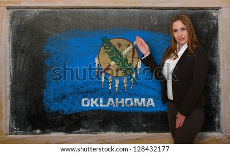 Successful, beautiful and confident woman showing flag of oklahoma on blackboard for marketing research, presentation and tourist advertising - stock photo