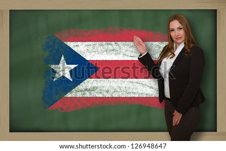 Successful, beautiful and confident woman showing flag of puertorico on blackboard for marketing research, presentation and tourist advertising - stock photo