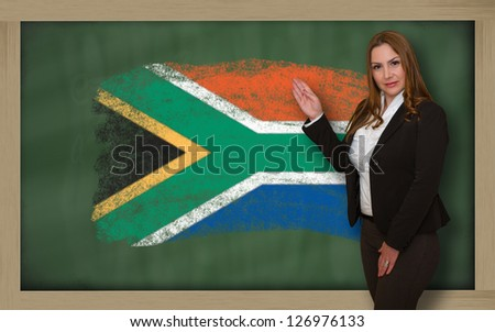 Successful, beautiful and confident woman showing flag of south africa on blackboard for marketing research, presentation and tourist advertising - stock photo