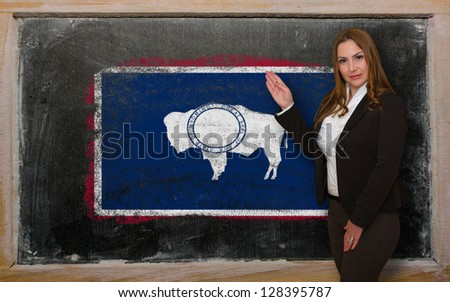 Successful, beautiful and confident woman showing flag of wyoming on blackboard for marketing research, presentation and tourist advertising - stock photo