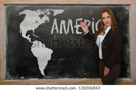 Successful, beautiful and confident young woman showing map of america on blackboard for presentation, marketing research and tourist advertising - stock photo
