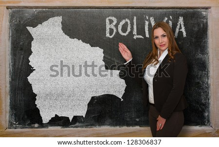Successful, beautiful and confident young woman showing map of bolivia on blackboard for presentation, marketing research and tourist advertising - stock photo