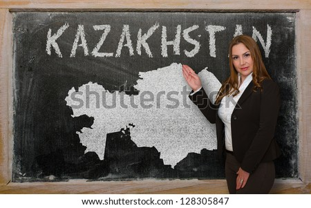 Successful, beautiful and confident young woman showing map of kazakhstan on blackboard for presentation, marketing research and tourist advertising - stock photo
