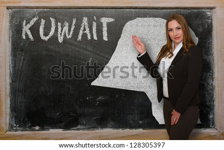 Successful, beautiful and confident young woman showing map of kuwait on blackboard for presentation, marketing research and tourist advertising - stock photo