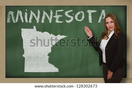 Successful, beautiful and confident young woman showing map of minnesota on blackboard for presentation, marketing research and tourist advertising - stock photo