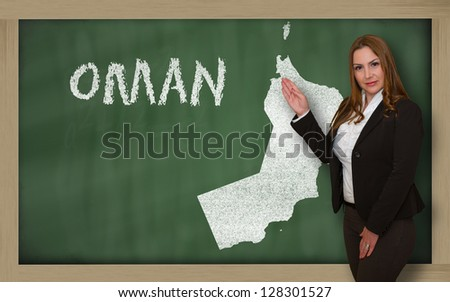 Successful, beautiful and confident young woman showing map of oman on blackboard for presentation, marketing research and tourist advertising - stock photo