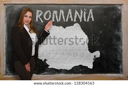 Successful, beautiful and confident young woman showing map of romania on blackboard for presentation, marketing research and tourist advertising - stock photo
