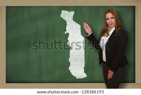Successful, beautiful and confident young woman showing map of togo on blackboard for presentation, marketing research and tourist advertising - stock photo