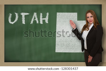 Successful, beautiful and confident young woman showing map of utah on blackboard for presentation, marketing research and tourist advertising - stock photo
