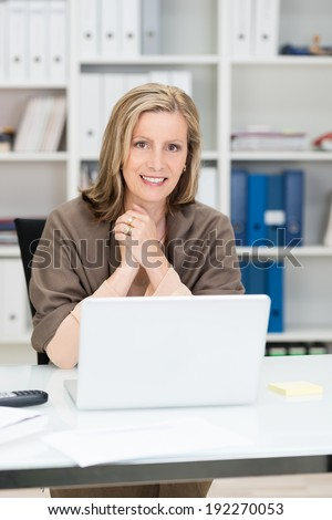Successful beautiful middle-aged businesswoman with a friendly smile sitting at her desk in the office looking at the camera over her laptop computer - stock photo