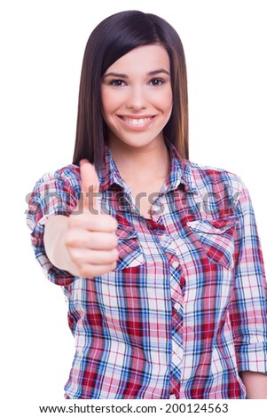 Successful beauty. Beautiful young smiling woman looking at camera and showing her thumb up while standing isolated on white - stock photo