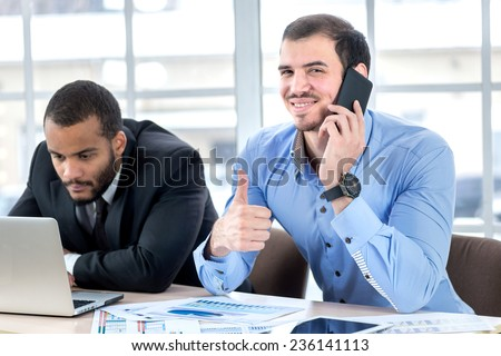 Successful business call. Smiling business people calling on a cell phone and showing thumb up while his colleagues are working at a laptop at his desk in the office in the formal wear. - stock photo