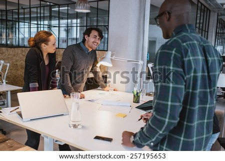 Successful business colleagues standing together at a meeting. Multiracial creative team  discussing work while standing at a table in office. - stock photo