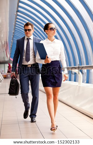 Successful business couple under an umbrella on a super white  - stock photo