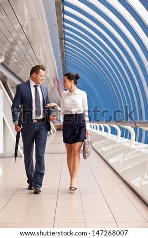 Successful business couple walk down the hall in the business center - stock photo