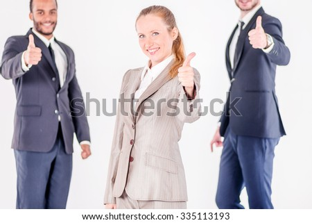 Successful business day. Three confident and successful businessman standing with hands clasped while businessman showing a thumbs up on a gray background - stock photo