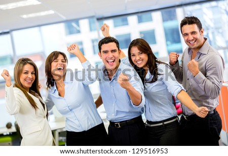 Successful business group with arms up at the office - stock photo