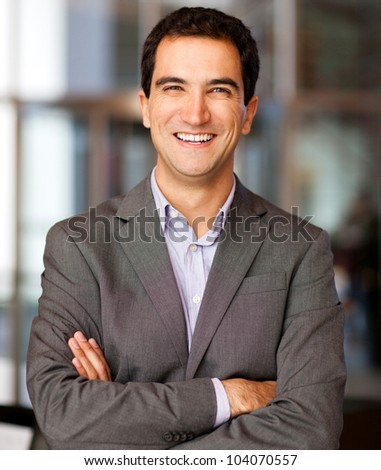 Successful business man smiling and looking friendly - stock photo