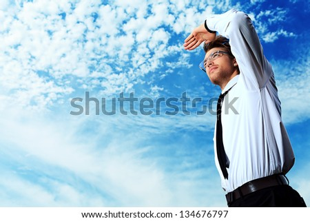 Successful business man standing over blue sky and purposefully looking away. - stock photo