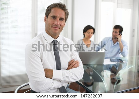 Successful business man standing with his staff in background at - stock photo