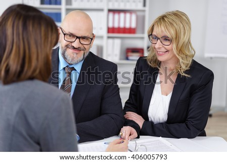 Successful business partners having a meeting seated together at a table in the office smiling as they have a brainstorming session developing ideas - stock photo