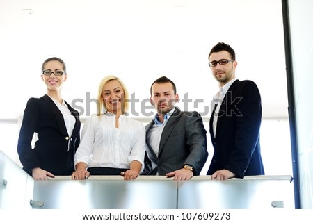 Successful business people standing on railing - stock photo