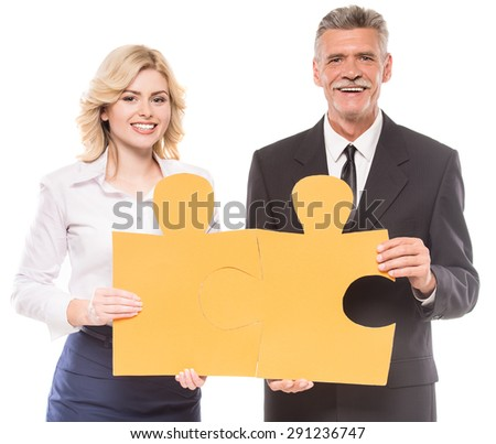 Successful business people wanting to put two big pieces of puzzle together. - stock photo