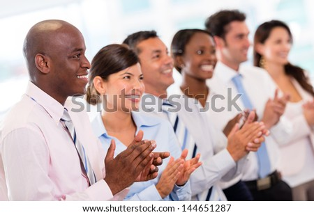 Successful business presentation and a group of people applauding - stock photo