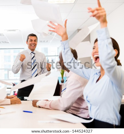 Successful business team celebrating at the office in a meeting - stock photo