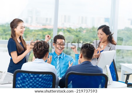 Successful business team celebrating in the office - stock photo