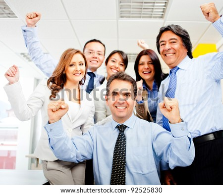 Successful business team celebrating with arms up at the office - stock photo