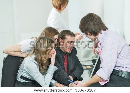 Successful business team conducts discussion in front of computer in office. Funny moment - stock photo