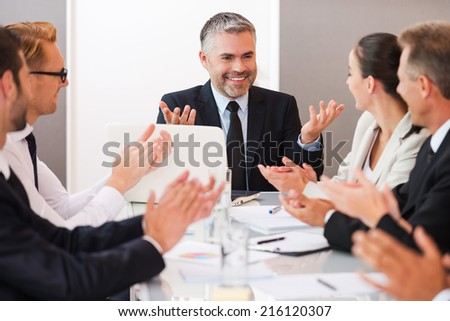 Successful business team. Confident mature man in formalwear smiling and gesturing while his colleagues applauding to him - stock photo