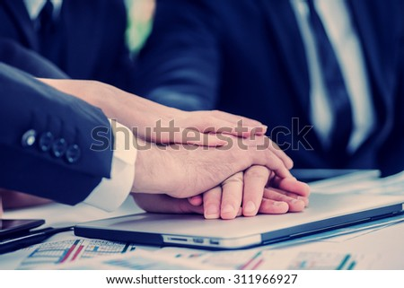 Successful business team. Four confident successful businessmen at a meeting while sitting at a table discussing business affairs in the office and laid their hands on hands - stock photo