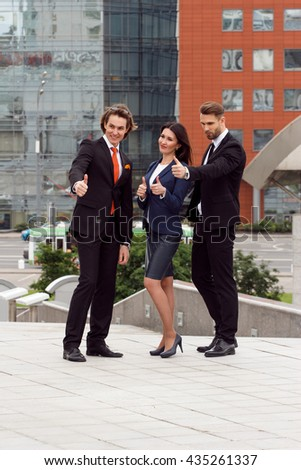 Successful business team. Full length of group of confident business people showing thumbs up standing close to each other and smiling.  - stock photo