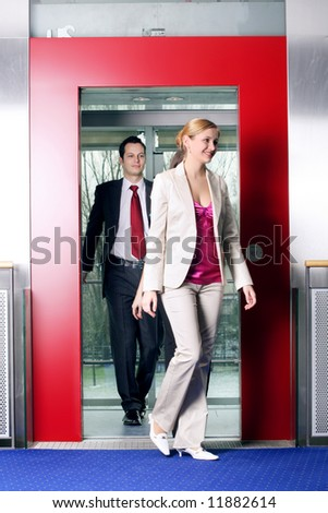 successful business team going on a lift is talking - stock photo