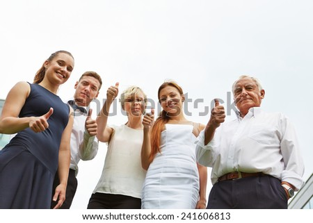 Successful business team holding thumbs up and smiling - stock photo