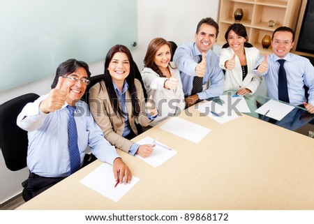 Successful business team in a meeting with thumbs up - stock photo