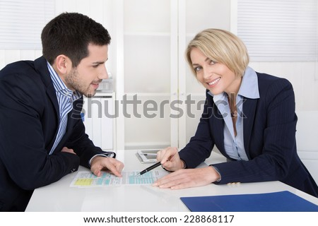 Successful business team in the yearly performance review talk sitting at desk. - stock photo