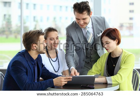 Successful business team of four sitting in office and planning work - stock photo