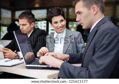 Successful business team of three sitting at the table in cafe - stock photo