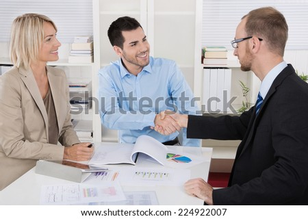 Successful business team sitting around a table in a meeting. - stock photo
