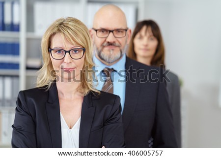 Successful business team with diverse professionals with a man and two women and focus to a team leader or manageress in the foreground - stock photo
