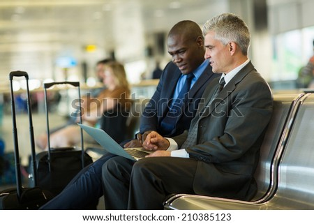successful business travelers using laptop at airport - stock photo