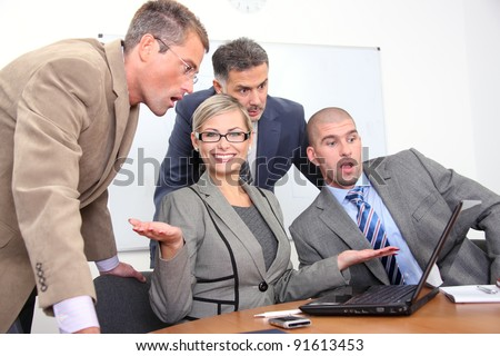 Successful business woman and her impressed colleagues in a meeting at office - stock photo