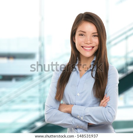 Successful business woman confident portrait. Female businesswoman standing proud and cross-armed looking at camera. Multiracial Asian Chinese / Caucasian female in her 20s. - stock photo