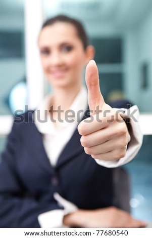 successful business woman giving a thumbs up (thumb in focus) - stock photo